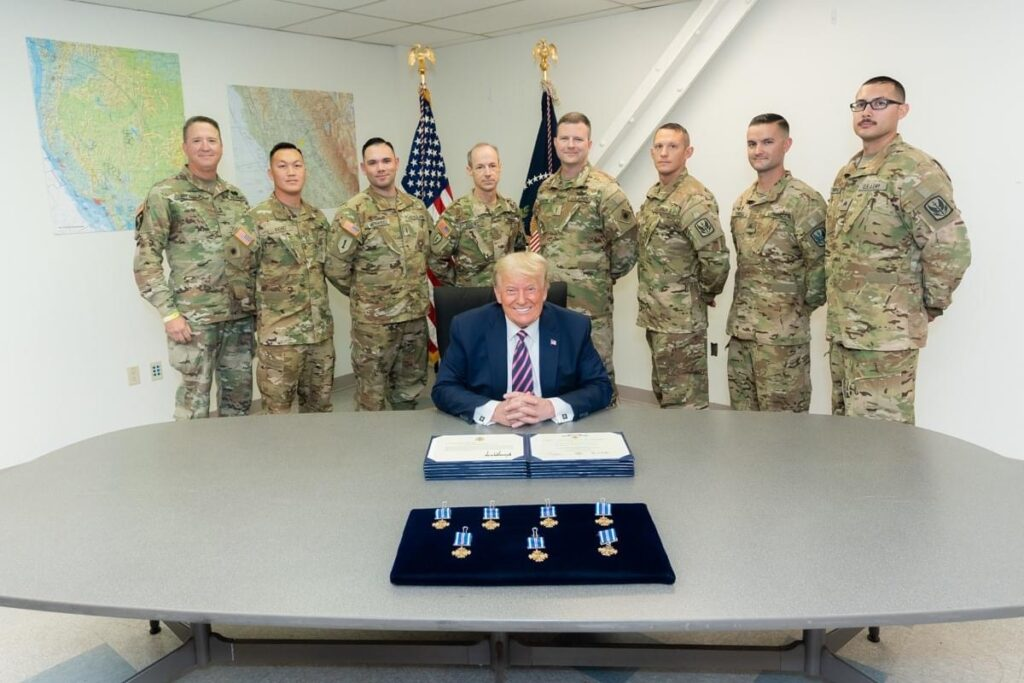 Recipients of the Distinguished Flying Cross Chief Warrant Officers Joseph Rosamond, Kipp Goding, Irvin Hernandez, Brady Hlebain, Ge Xiong; and Sergeants George Esquivel and Cameron Powell with Major General Matthew Beavers (center) for their role in the Creek Fire rescue at Mammoth Pools Reservoir pose with President Donald Trump, who personally awarded each member of the crew their award.
